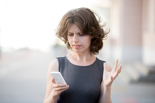 Confused woman looking at iPhone.