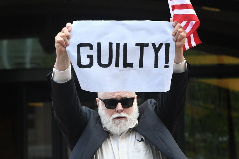 """A bearded man with sunglasses holding a large white cloth reading """"Guilty"""""""
