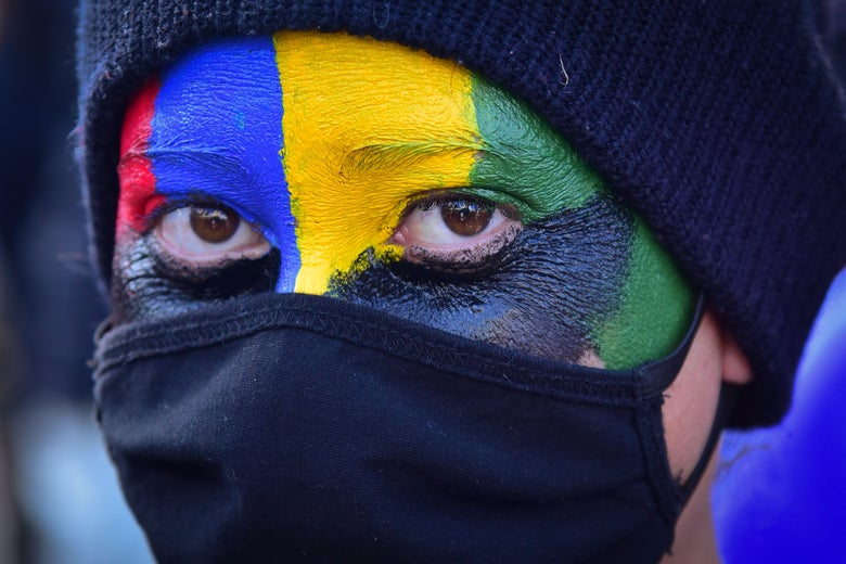A close-up view of a woman in a hat and face mask, with her only visible skin painted in red, blue, yellow, green, and black.