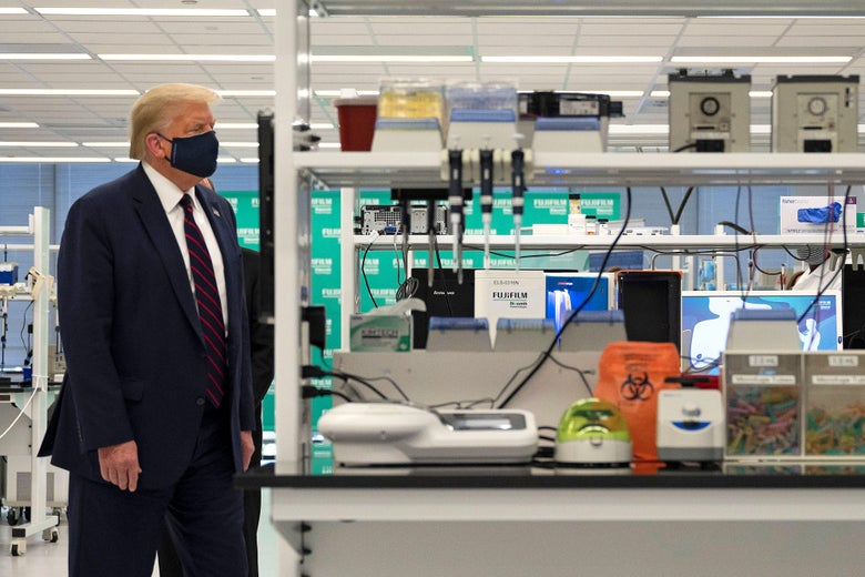 Trump wears a suit and a mask as he walks by scientific equipment.