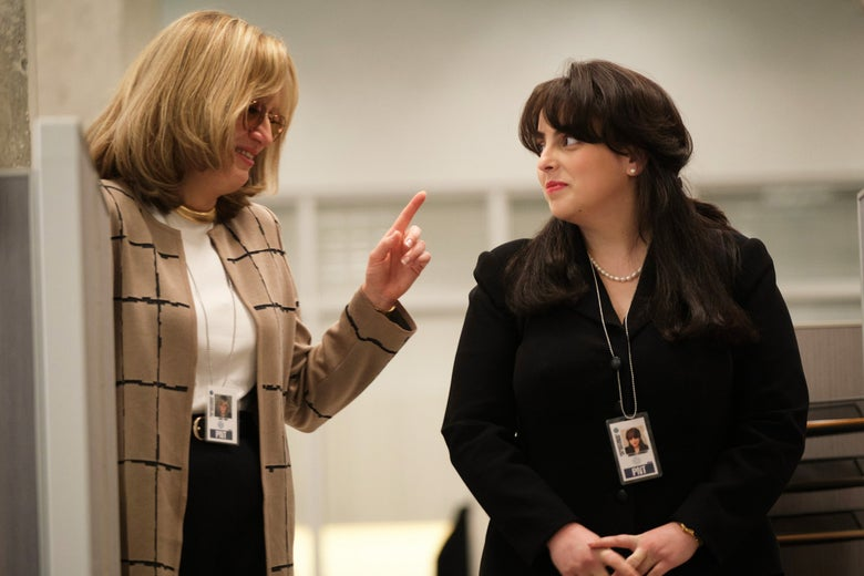Sarah Paulson as Linda Tripp raises her left index finger at Beanie Feldstein as Monica Lewinsky as they stand together in an office, smiling collegially