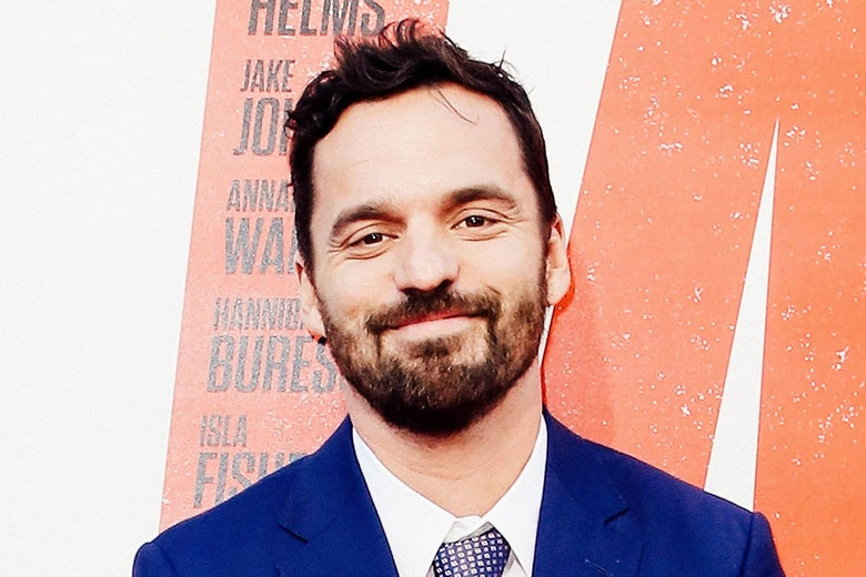 Jake Johnson smiles with a closed mouth.