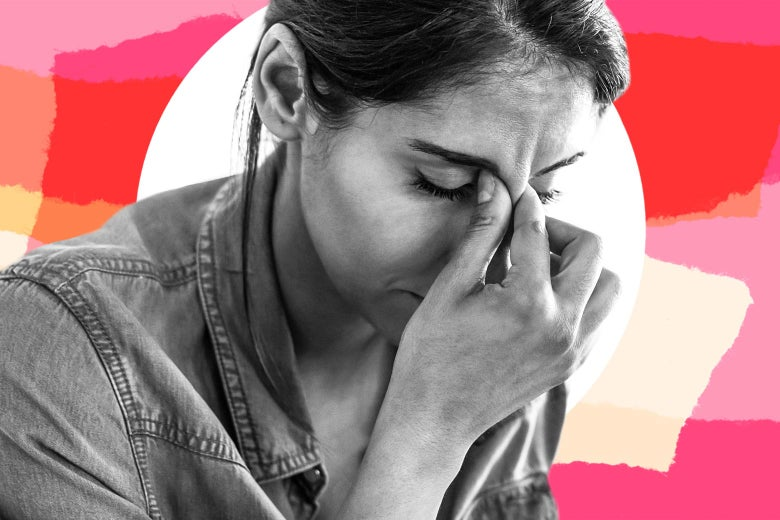 A woman pinches the bridge of her nose and closes her eyes. She looks distressed.