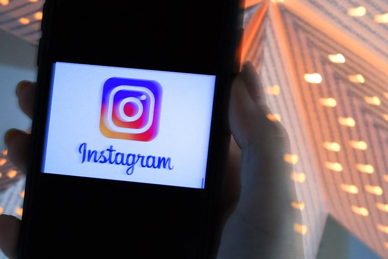 In this photo illustration, a person looks at a smart phone with a Instagram logo displayed on the screen