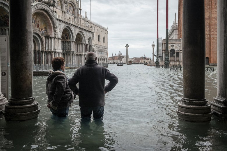 Two people observe a flooded St. Mark's Square, with water reaching their thighs, Nov 15th 2019, Venice.