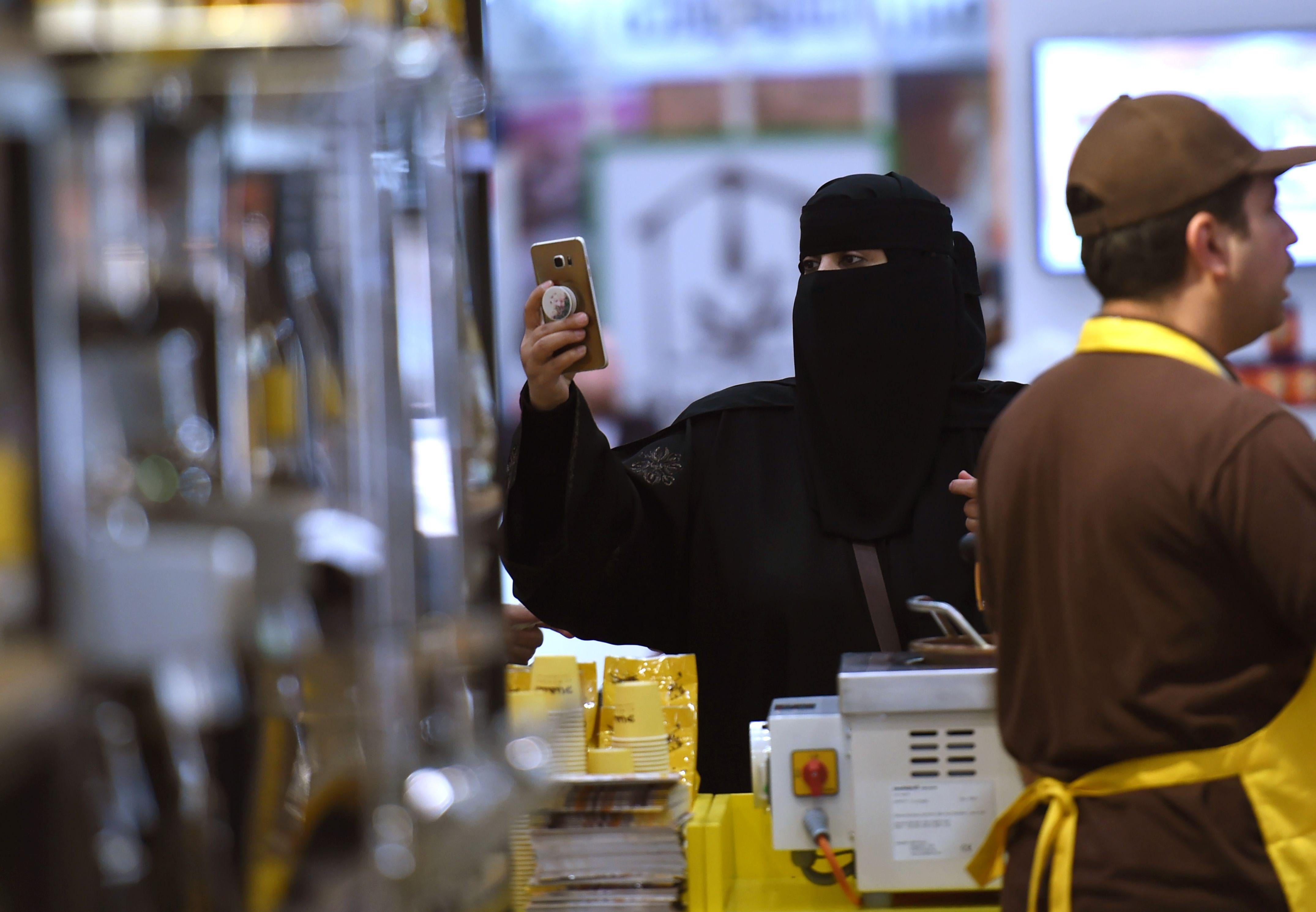 A Saudi woman holds up her cellphone next to a stand at the International Coffee and Chocolate Exhibition.