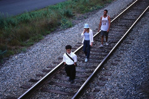A movie still featuring three people on a train track.