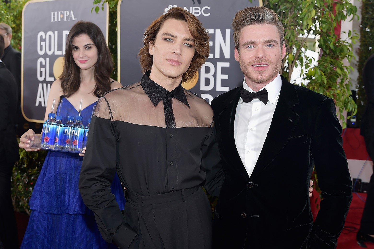 Actors Cody Fern and Richard Madden photobombed by Fiji Water Girl at the 76th Annual Golden Globe Awards on January 6, 2019 at the Beverly Hilton in Los Angeles, California.