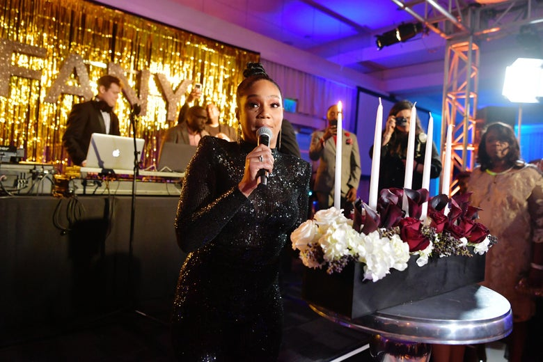 Tiffany Haddish holds a microphone and stands in front of candles at a party to celebrate her bat mitzvah.