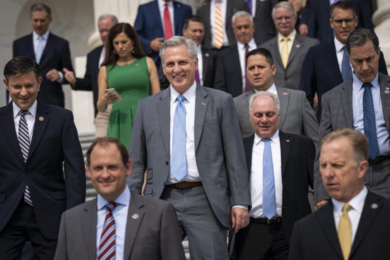 A bunch of old white men in suits walking down stairs, along with one white woman