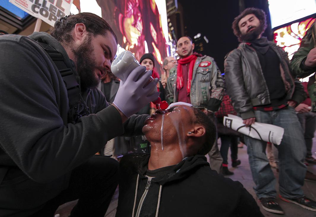 A man helps a protester who was pepper-sprayed as the protesters block Fifth Avenue during protests in New York City on Nov. 25, 2014