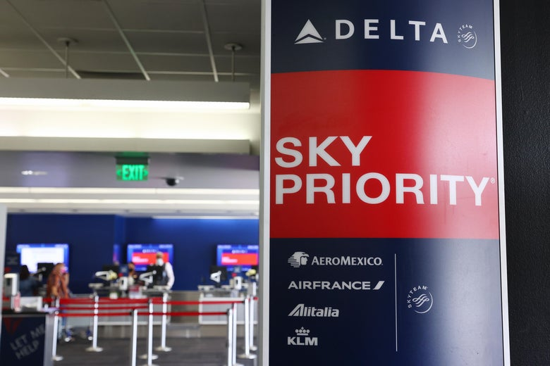 LOS ANGELES, CALIFORNIA - AUGUST 25: A Delta Air Lines sign is displayed on the departures level at Los Angeles International Airport (LAX) on August 25, 2021 in Los Angeles, California. Delta is increasing health insurance premiums for employees who are unvaccinated by $200 per month to cover higher costs of Covid-related care. (Photo by Mario Tama/Getty Images)