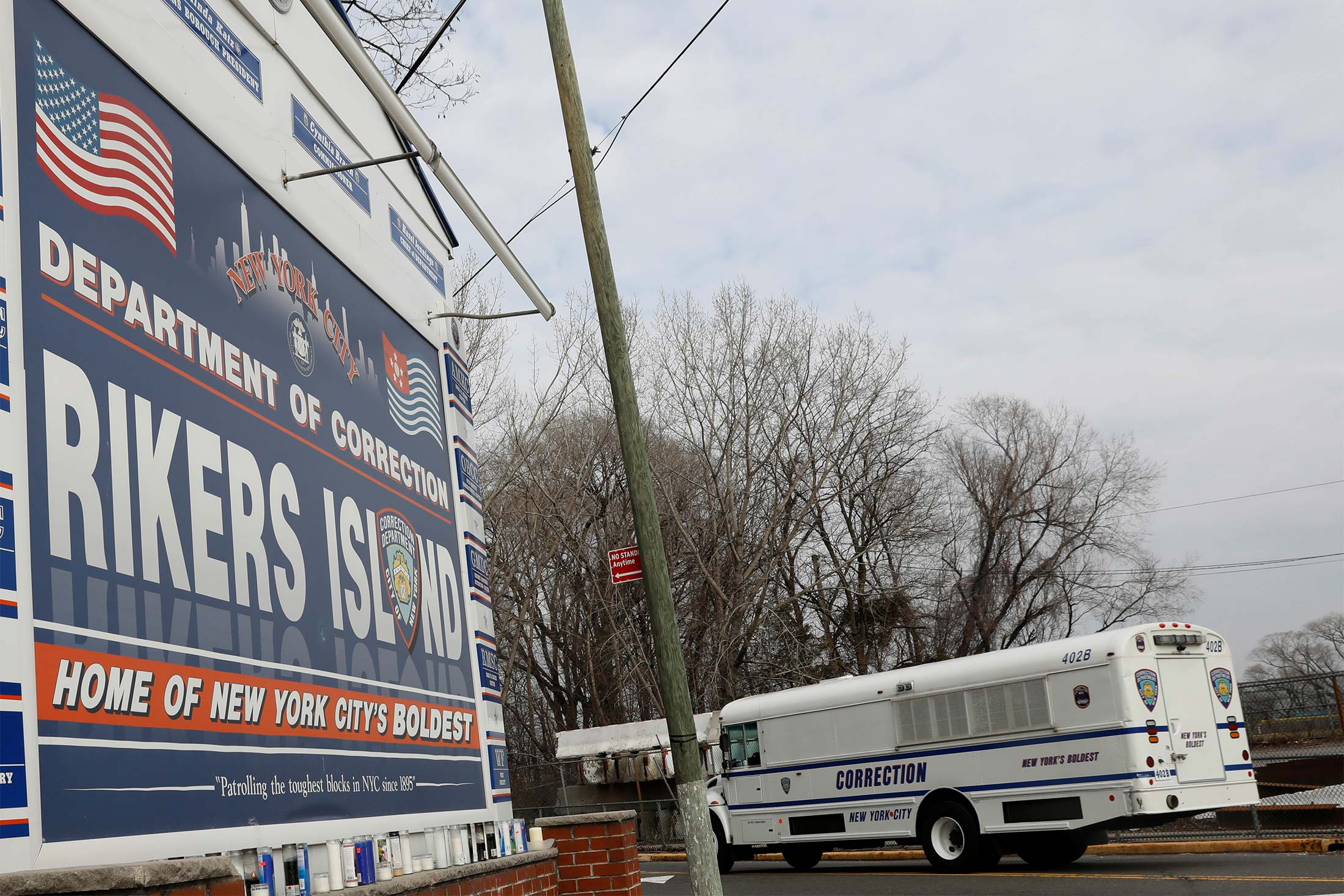 A white bus with the word CORRECTION on it in large letters drives past a Rikers Island sign.