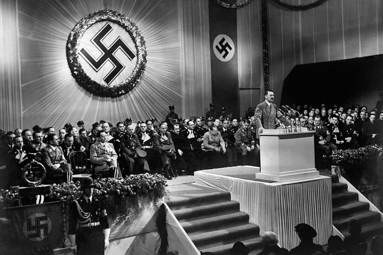 Hitler speaks from a crowded dais in front of a large Nazi insignia.