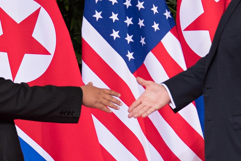 Kim Jong-un and Donald Trump shake hands in front of North Korean and U.S. flags.