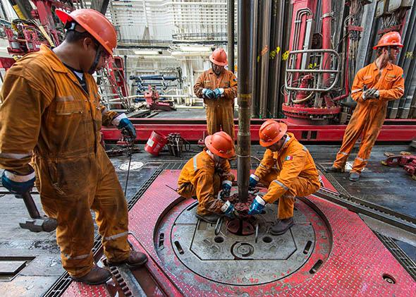 A team removes a drilling tool with a sample of the marine seabed at an oil rig in the Gulf of Mexico