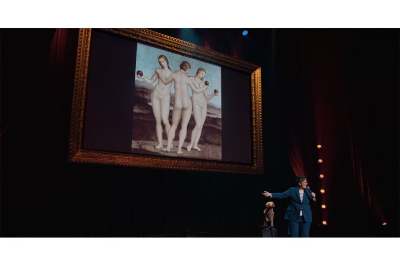 Hannah Gadsby standing in front of an image of Raphael's Three Graces.
