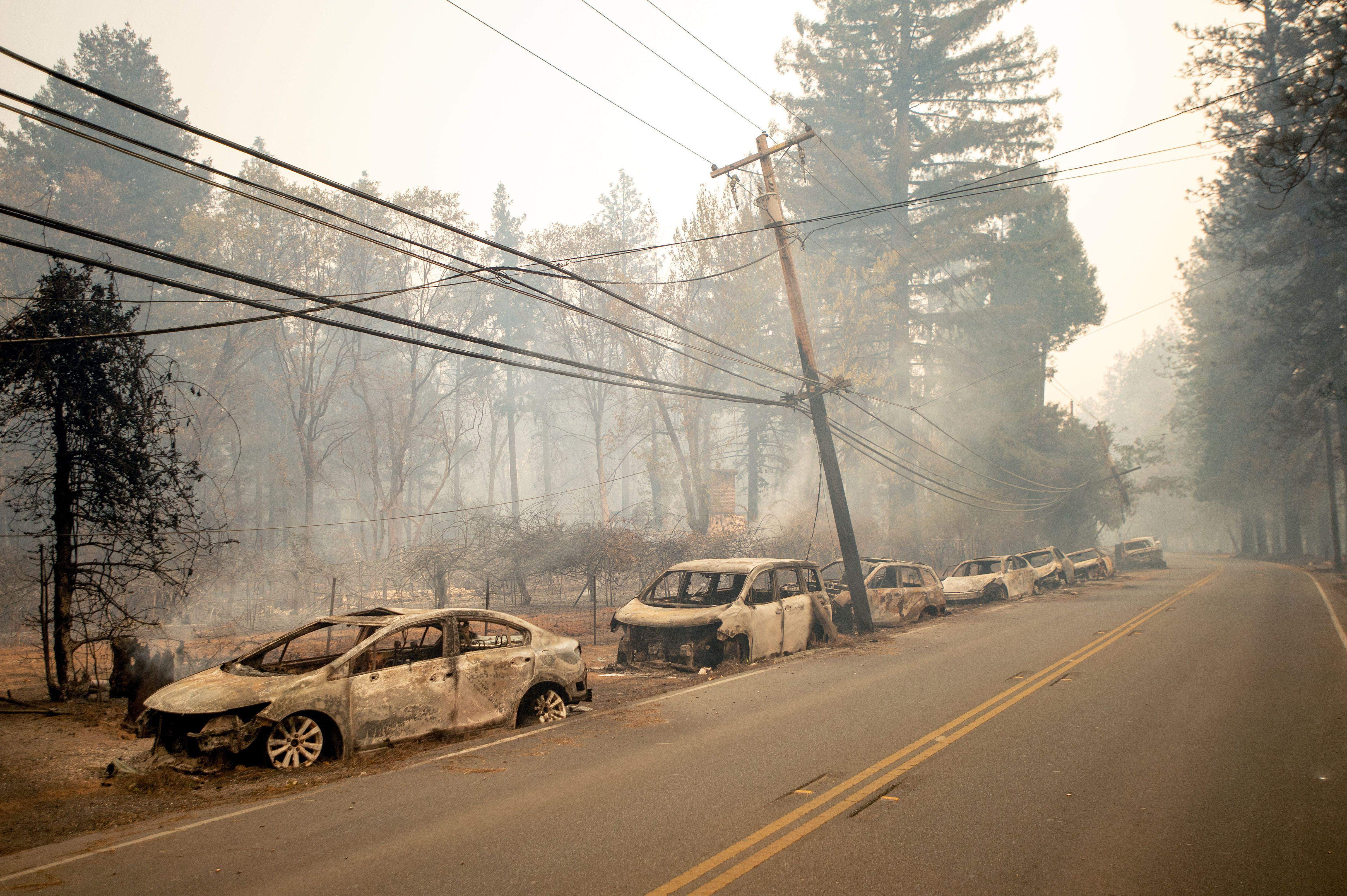 Abandoned and charred vehicles sit on the side of a road. An electrical pole leans dangerously. The air is hazy.