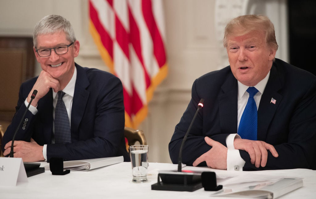 Tim Cook and Donald Trump, wearing suits, sit at a conference table in front of an American flag.