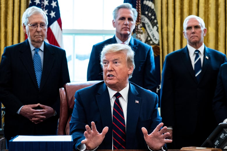 Mitch McConnell, Kevin McCarthy, and Mike Pence stand behind Donald Trump, who is sitting at his desk and speaking with his hands raised.