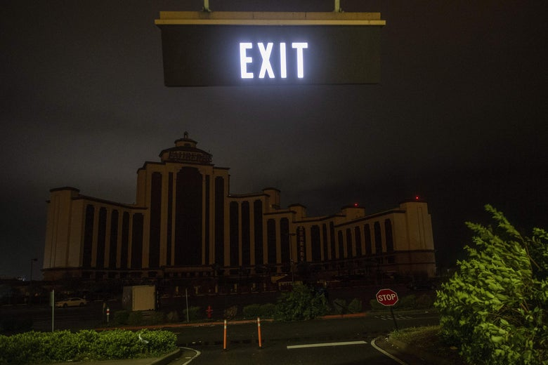 A dark hotel is seen with a lit Exit sign overhead.