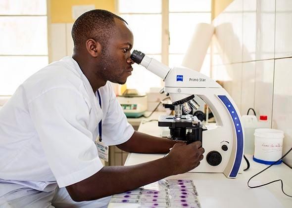 Laboratory assistant working with a microscope at the Ngoma health center on February 5, 2014 in Ngoma, Rwanda.