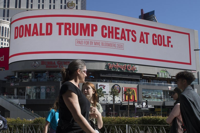 People walk past a billboard paid for by Democratic presidential hopeful Mike Bloomberg saying Trump cheats at golf.