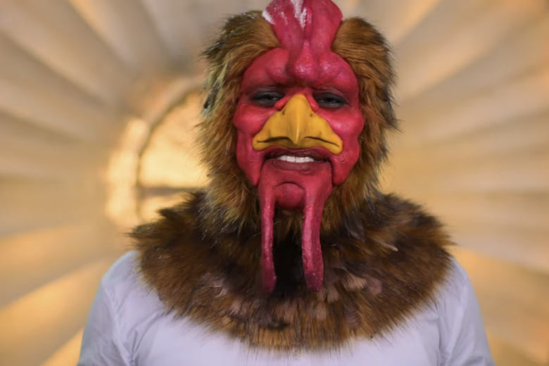 Man in white shirt smiling at the camera while wearing a rooster head.