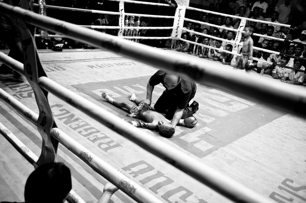 Bank has lost the boxing match against Tountong and is lying unconscious on the ground.