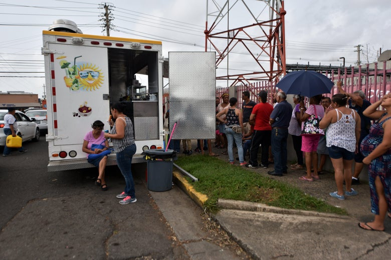 People wait to buy food from a foodtruck, in Humacao, in the east of Puerto Rico, on September 27, 2017.          The US island territory, working without electricity, is struggling to dig out and clean up from its disastrous brush with the hurricane, blamed for at least 33 deaths across the Caribbean.          / AFP PHOTO / HECTOR RETAMAL        (Photo credit should read HECTOR RETAMAL/AFP/Getty Images)