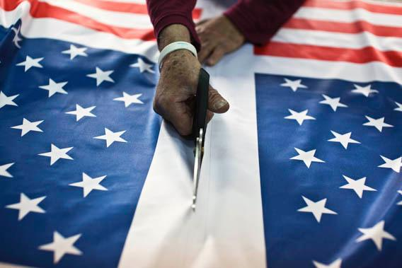 A worker at a factory in Kfar Saba near Tel Aviv cuts fabric printed with U.S. flags ordered ahead of President Barack Obama's visit to Israel March 12, 2013.