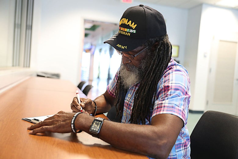 A man in a Vietnam veteran hat fills out paperwork in an office.