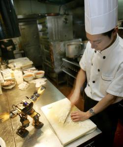 A robot performs pre-programed actions as a chef (R) prepares food in the Robot Kitchen restaurant.
