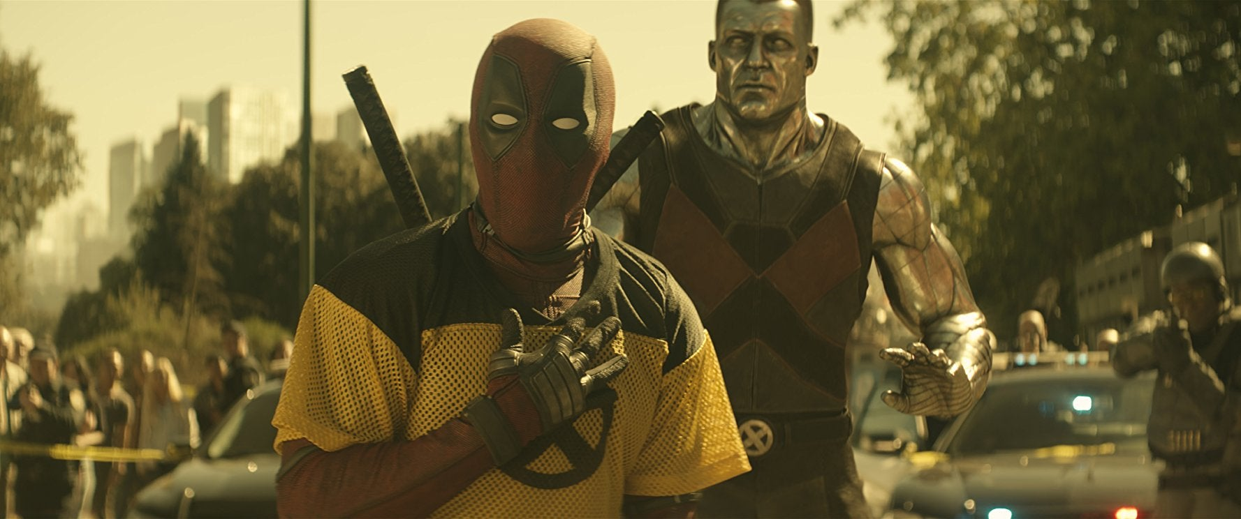 Deadpool, wearing his red suit and mask, stands in front of Colossus in a still from Deadpool 2.