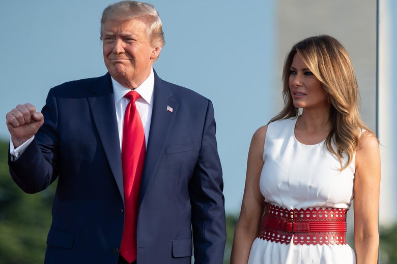 Donald and Melania Trump stand while holding hands, the former also raising a fist.