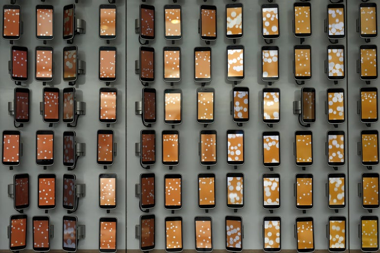 Smartphones hang on a wall at the Mobile World Congress (MWC), the world's biggest mobile fair, on February 28, 2018 in Barcelona.