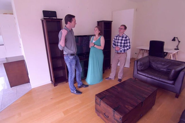 "A couple standing in a living room talking to a ""relocation expert."""