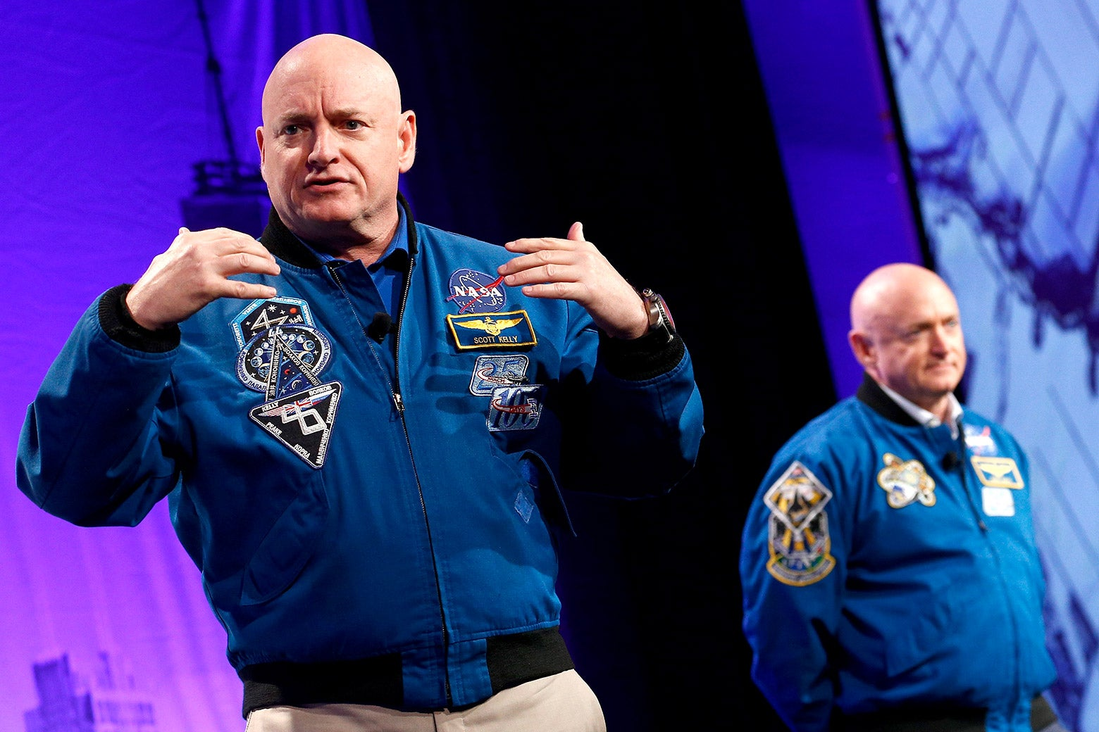 Astronauts Capt. Scott Kelly and Capt. Mark Kelly speak onstage.
