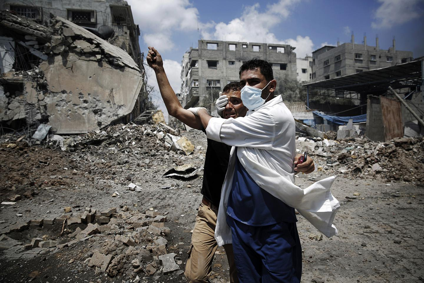 A medic helps a Palestinian in the Shejaia neighborhood, which was heavily shelled by Israel during fighting, in Gaza City.