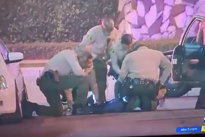 Four uniformed officers surround the reporter lying face-down on the pavement