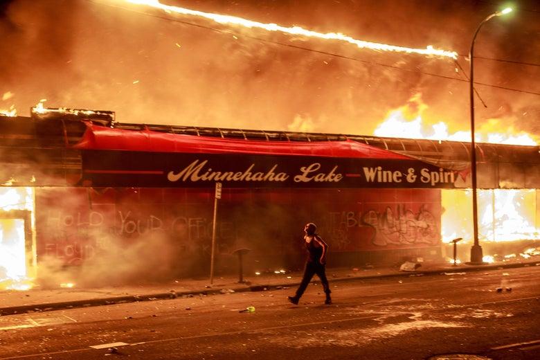A man walks past a burning building