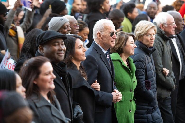 Tulsi Gabbard, Joe Biden, Amy Klobuchar, Elizabeth Warren, and Bernie Sanders link arms in a row of marchers.