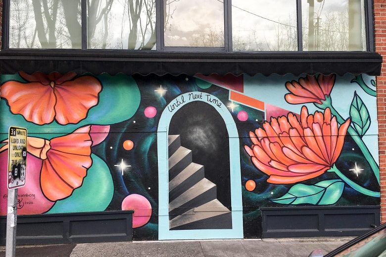 A mural of big red-orange flowers surrounding a faux door and stairs.
