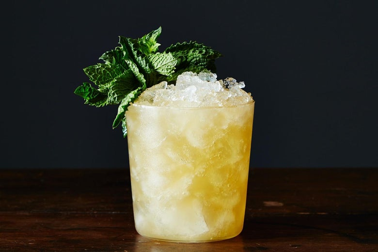A glass tumbler filled with crushed ice and a yellow-colored liquid, garnished with a mint leaf.
