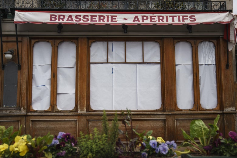 A restaurant is seen with covered windows.
