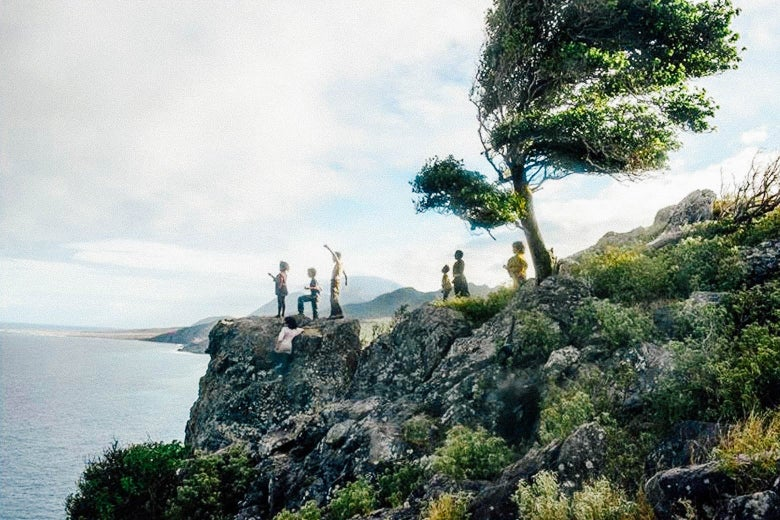 A scene from Wendy, in which a group of kids stand on a foliage-heavy cliff overlooking a body of water