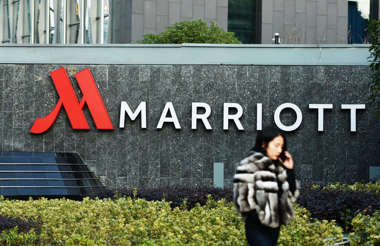 Woman walking past Marriott sign.