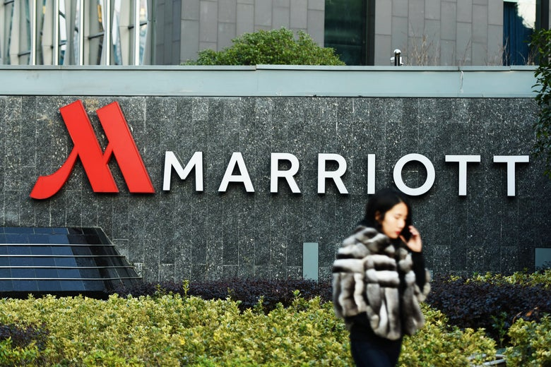 Woman walking past Marriott sign.