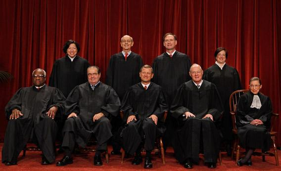 U.S. Supreme Court members pose for photographs in the Supreme Court building.