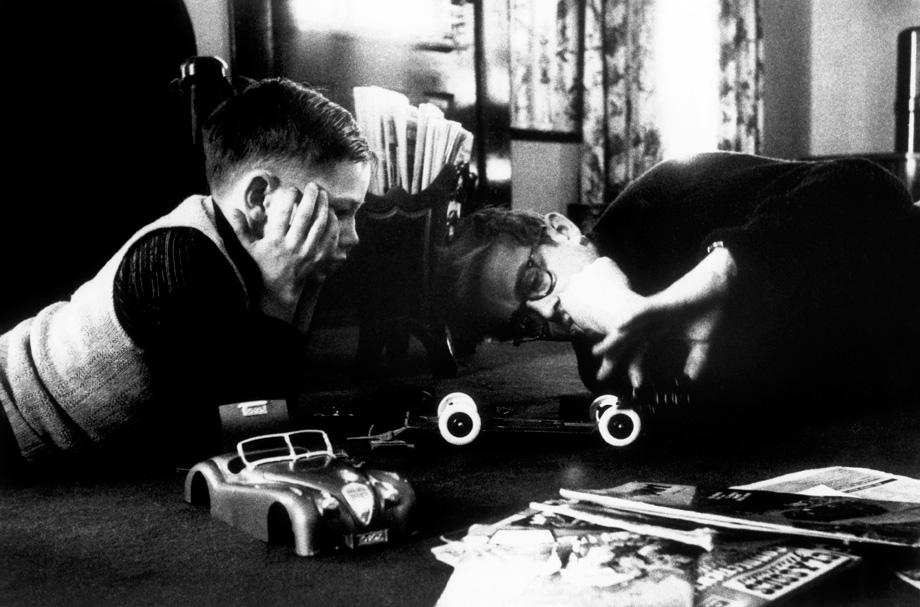 Fairmount, Indiana. James Dean and his young cousin Markie play with a model car. 1955.